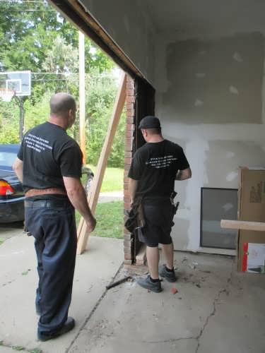 "alt="" two five star doors technicians installing a replacement garage door"""