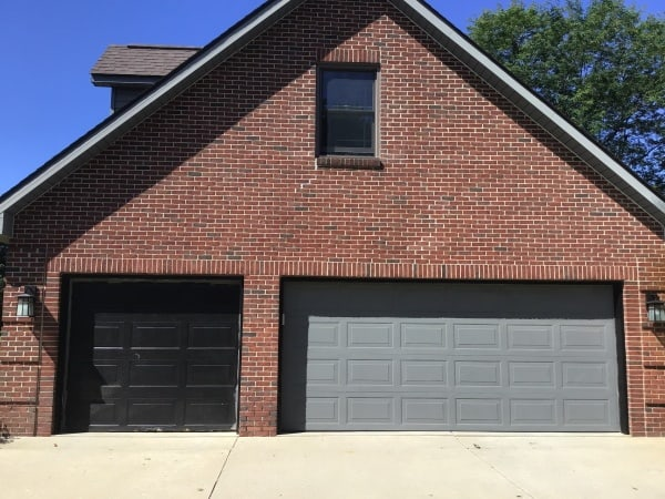 "alt="" a 30 year old double Amarr garage door painted grey and a black single door on a red brick colonial home in South Lyon"""