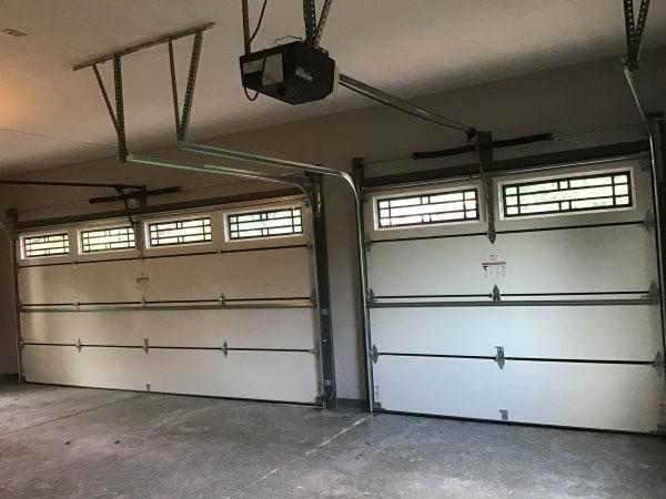"alt="" inside of a garage showing off two new Amarr Lincoln 3000 garage doors."