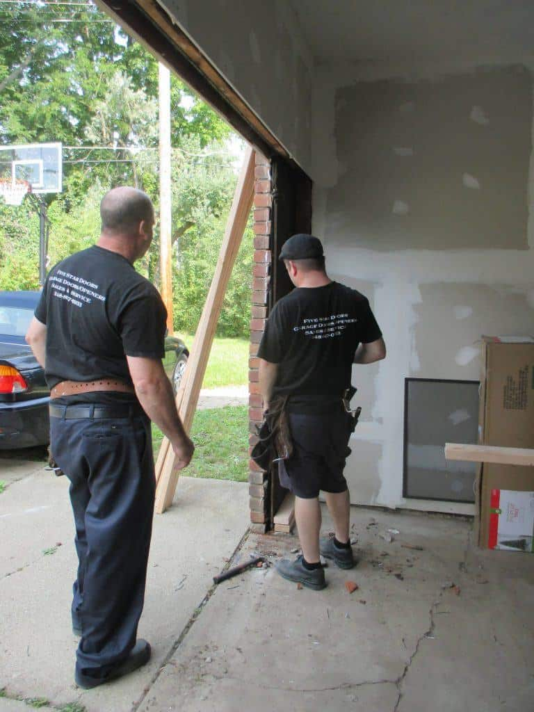 "alt=""Shane and Andrew working on a garage door in South Lyon, Michigan"""